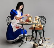 Young woman sitting at table serving tea