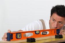 Man measuring plank of wood.