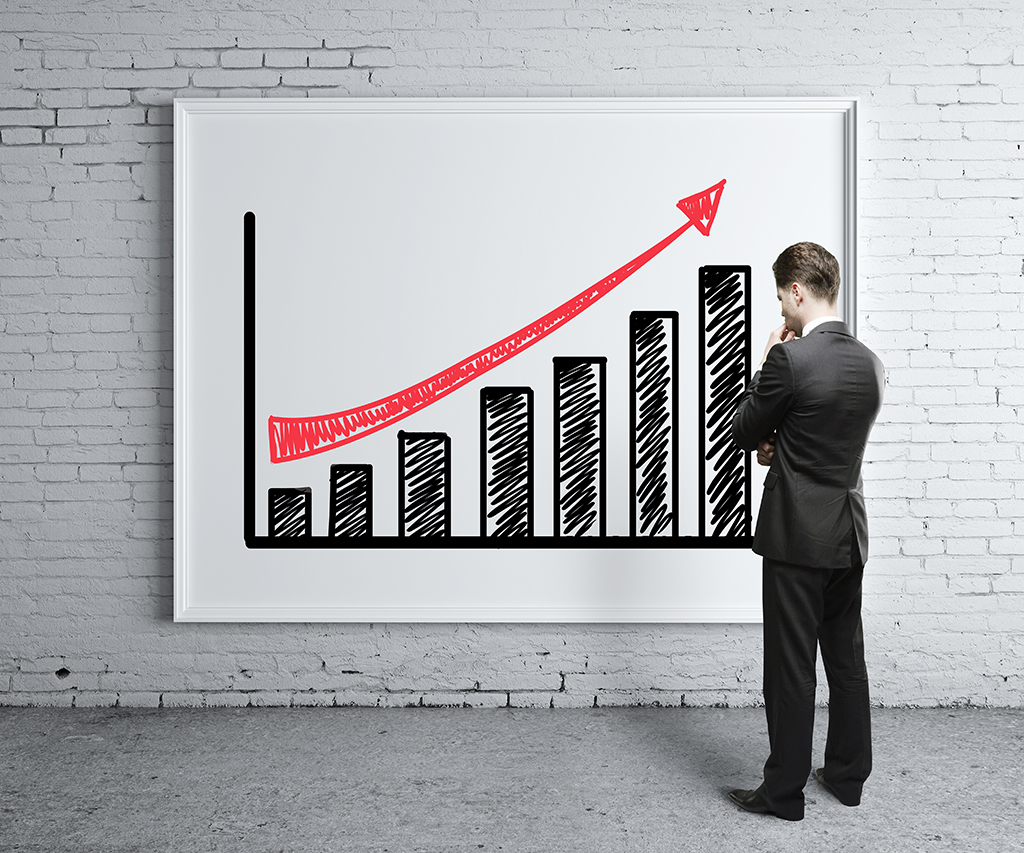 businessman looking at growth chart on desk