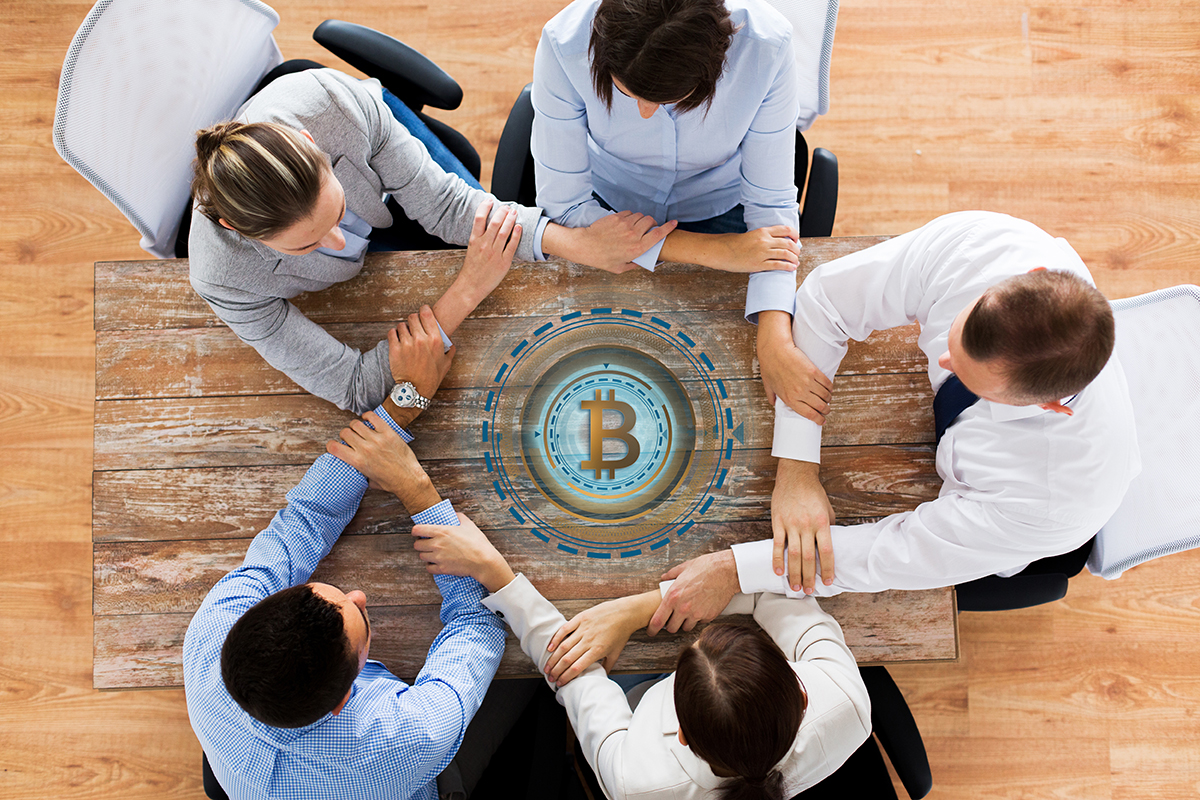 cryptocurrency, cooperation and finance concept concept - business team sitting at office table with bitcoin hologram and holding hands from top