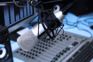 A mic in front of the control panel in broadcasting studio